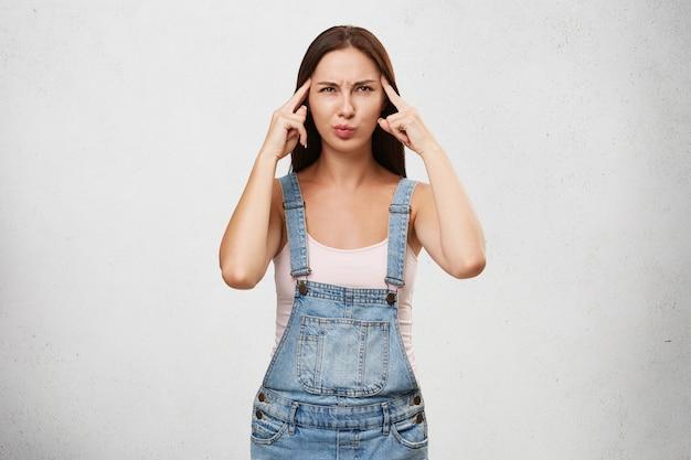 Gedachten, concentratie en focus concept. beeld van grappige jonge kaukasische vrouw in modieuze kleren die blik hebben geconcentreerd Gratis Foto