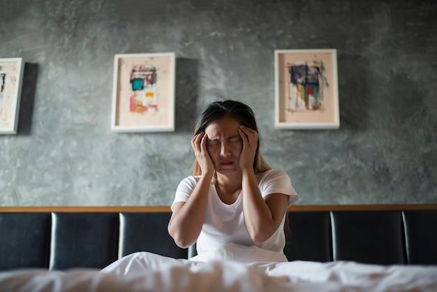 Gedeprimeerde vrouw met hoofdpijnhand die haar hoofd op het bed houdt Gratis Foto