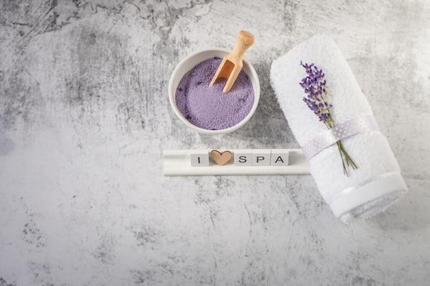 Gedraaide badhanddoek met badzout en houten letters spelling i love spa. Premium Foto