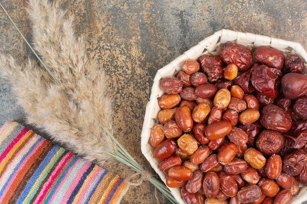 Gedroogd fruit met kleurrijk tafelkleed op marmeren achtergrond. foto van hoge kwaliteit Gratis Foto