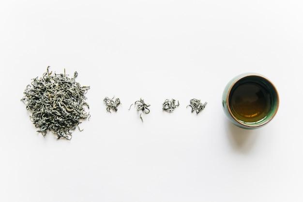 Gedroogd theekruid met theekopje dat op witte achtergrond wordt geïsoleerd Gratis Foto
