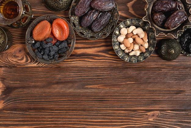 Gedroogde abrikoos; zwarte rozijn; dadels en thee op metalen kom op houten tafel Gratis Foto