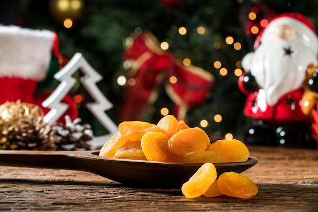 Gedroogde abrikozen in een kom op het bord met de achtergrond wazig kerstmis Premium Foto