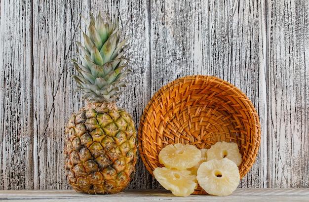 Gedroogde ananas met verse ananas in een mand op houten oppervlak Gratis Foto