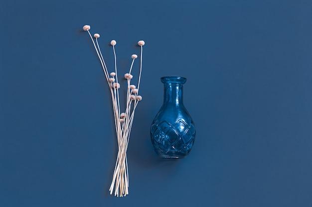 Gedroogde bloemen en een vaas op blauw. Gratis Foto