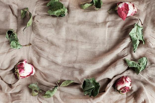 Gedroogde rozen en bladeren op beige stof achtergrond met kopie ruimte, bovenaanzicht Premium Foto
