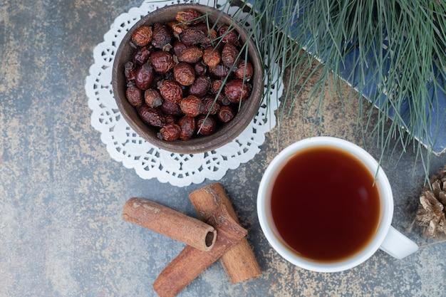 Gedroogde rozenbottels, kopje thee en kaneel op marmeren oppervlak. hoge kwaliteit foto Gratis Foto