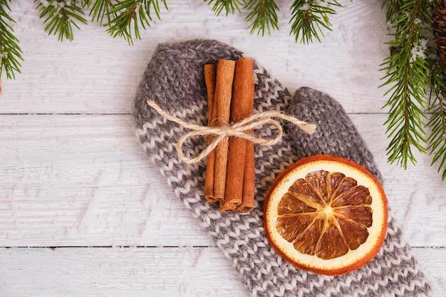 Gedroogde sinaasappel en kaneelstokjes op handschoen. houten kerst concept Premium Foto