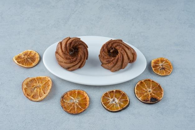Gedroogde sinaasappel met twee heerlijke cupcakes op witte achtergrond Gratis Foto