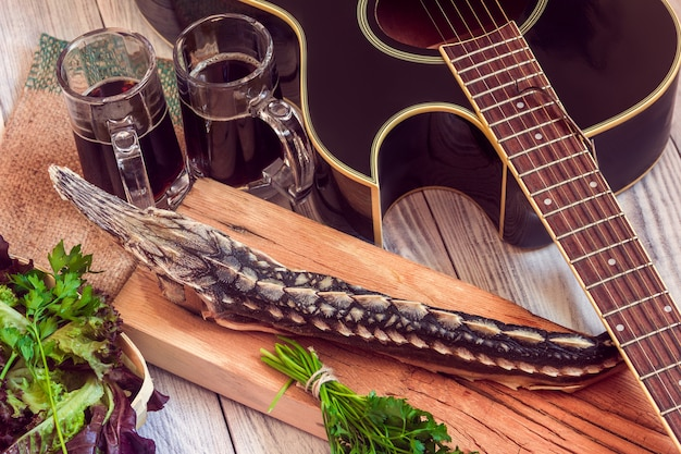 Gedroogde steur met donker bier, greens en gitaar Premium Foto