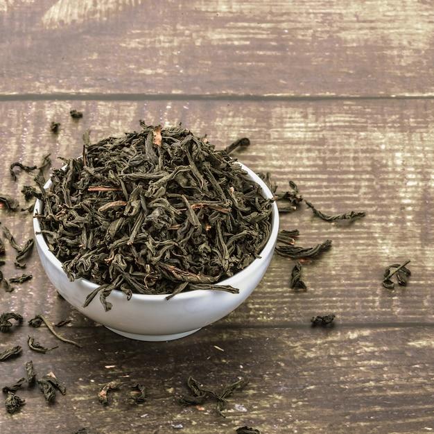 Gedroogde thee wordt gegoten in een keramische kop op een houten plank tafel. Premium Foto