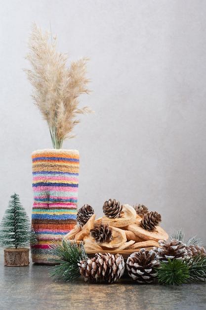 Gedroogde vruchten en pinecones in houten kom op marmeren achtergrond. foto van hoge kwaliteit Gratis Foto