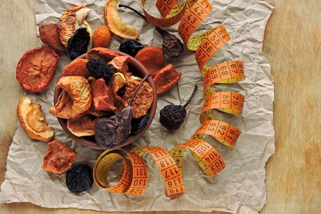 Gedroogde vruchten in een kom en meetlint. concept van gedroogd fruit voor een slank lichaam. Premium Foto