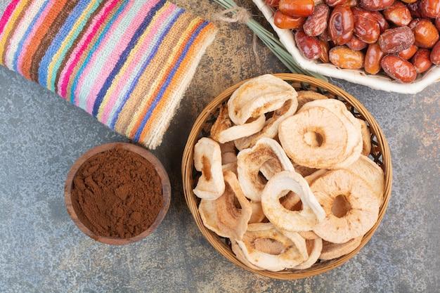 Gedroogde vruchten met cacaopoeder in houten kom op marmeren achtergrond. foto van hoge kwaliteit Gratis Foto