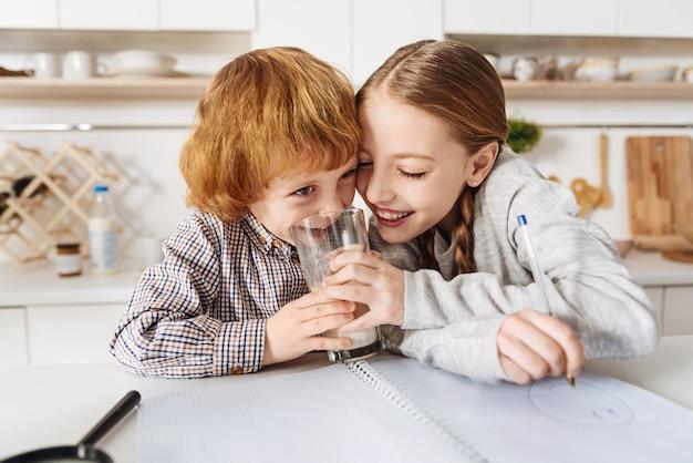Geef dat aan mij. leuke, mooie, mooie jongen die probeert wat melk van haar broers en zussen te drinken terwijl ze de ochtend in de keuken doorbrengen en plezier maken Premium Foto