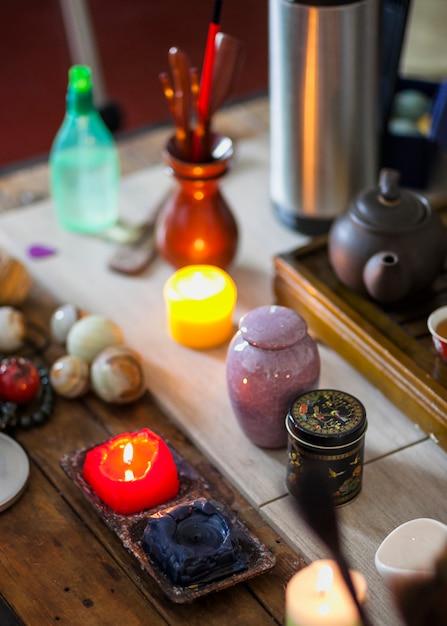 Geel; blauwe en rode brandende kaarsen met theeketel en knikkers meditatie ballen op houten tafel Gratis Foto