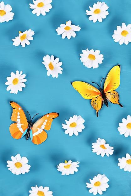 Geel en oranje vlinders en madeliefjes op blauwe achtergrond. bovenaanzicht. zomer achtergrond. Premium Foto