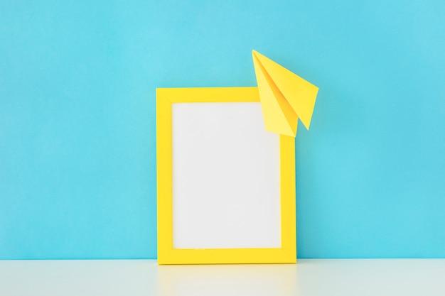 Geel fotokader en document vliegtuig voor blauwe muur Gratis Foto