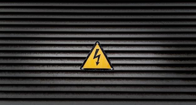 Geel gevaarsteken op een zwart gestreepte muur Gratis Foto