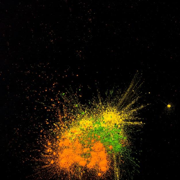 Geel, groen en oranje gekleurd poeder dat over zwarte achtergrond wordt verdeeld Gratis Foto
