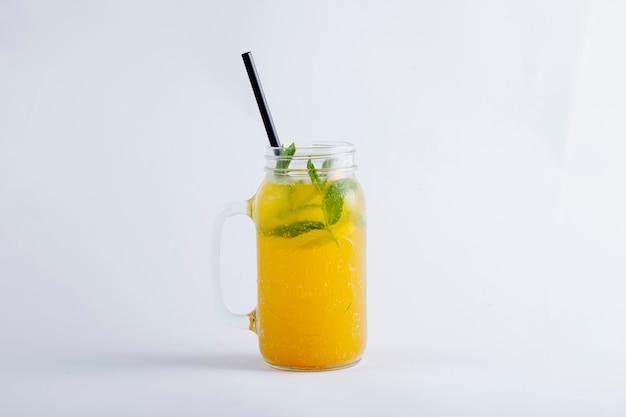 Geel jus d'orange in een glazen pot met muntblaadjes. Gratis Foto