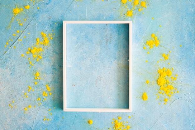 Geel kleurenpoeder rond het witte grenskader op geschilderde muur Gratis Foto