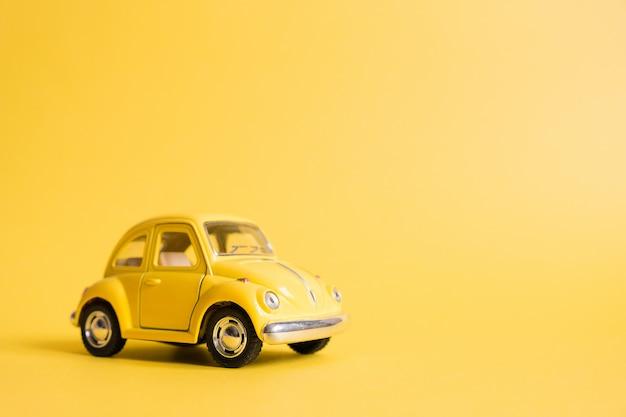 Geel. retro speelgoedauto op geel. zomer reizen concept. taxi Premium Foto