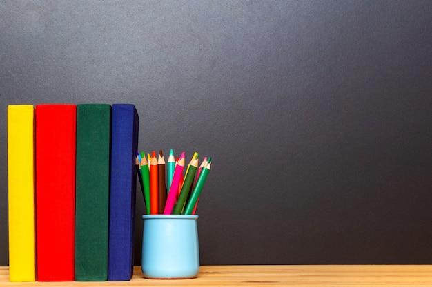 Geel rood groen en donkerblauw boeken met kleurrijke potloden voor schoolbord. terug naar school concept. onderwijs achtergrond. Premium Foto