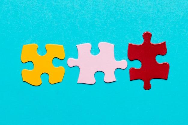 Geel; roze en rode puzzel stuk op blauwe gestructureerde achtergrond Gratis Foto