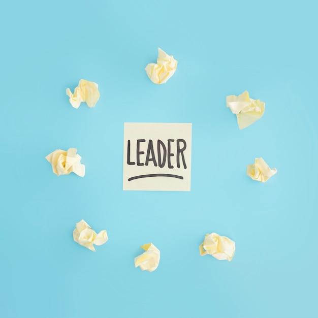 Geel verfrommeld die document rond de hechtende nota van de leiderstekst op blauwe achtergrond wordt omringd Gratis Foto