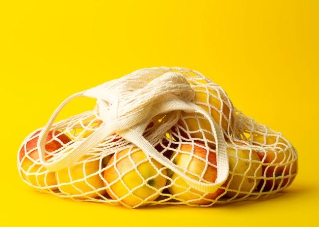 Geen afvalconcept. appelen in een koordzak op een gele achtergrond. geen plastic tassen in supermarkten en winkels concept Premium Foto