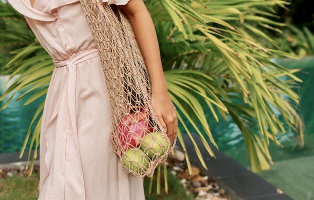 Geen afvalconcept. aziatische vrouw die eco vriendelijke mesh shopper met vers fruit. Gratis Foto