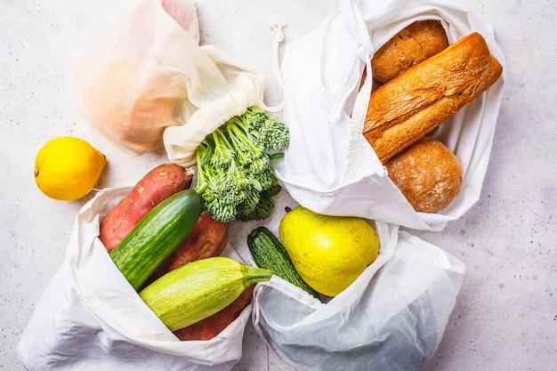 Geen afvalconcept. eco-zakken met fruit en groenten, eco-vriendelijke vegan platliggend, plasticvrij Premium Foto