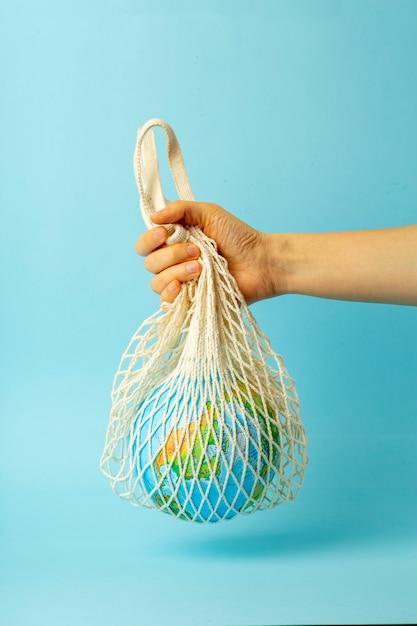 Geen afvalconcept. string tas in een vrouwelijke hand met earth globe. plastic zakken gratis Premium Foto