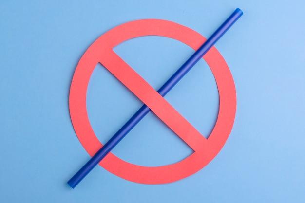 Geen plastic. klein blauw stro in verbodsteken over een blauwe achtergrond Premium Foto