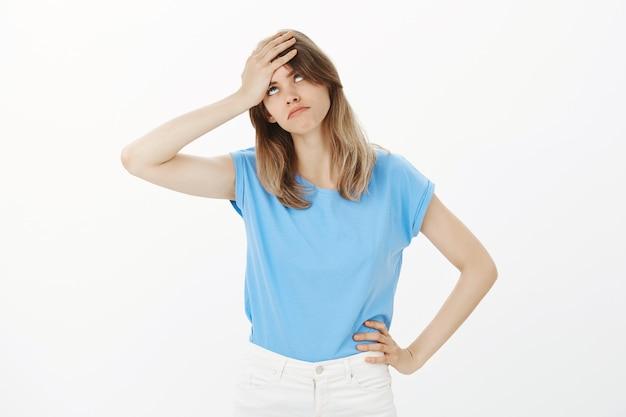 Geërgerd en gehinderd blonde vrouw oogrol en klap voorhoofd verontrust, kijkend geïrriteerd Gratis Foto