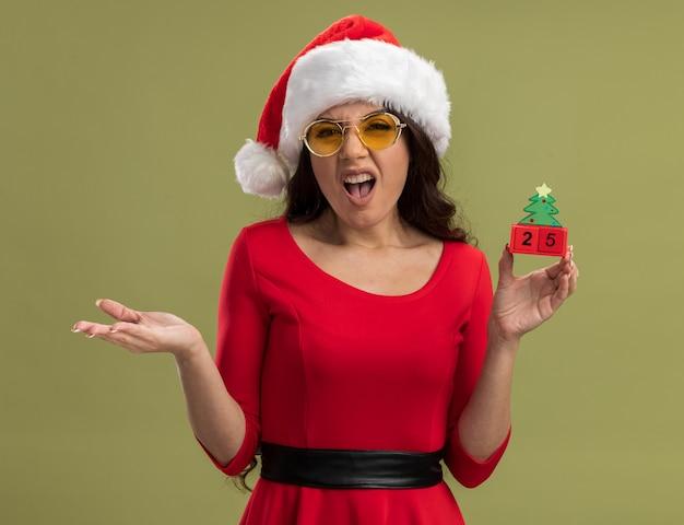 Geërgerd jong mooi meisje die santahoed en glazen dragen die kerstboomstuk speelgoed met datum houden die met lege hand kijken Gratis Foto