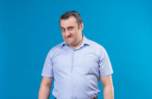 Geërgerd man van middelbare leeftijd in blauw shirt kijken naar de camera met een ontevreden uitdrukking op een blauwe ruimte Gratis Foto