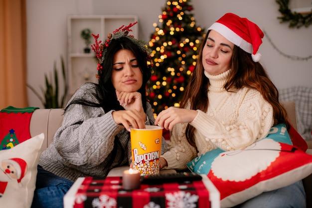Geërgerd mooie jonge meisjes met kerstmuts en hulstkrans eten en kijken naar popcornemmer zittend op fauteuils kersttijd thuis Gratis Foto