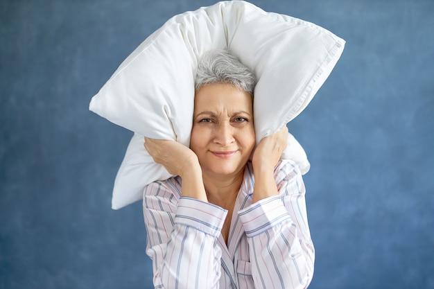 Geërgerd ontevreden volwassen vrouw met grijze haren grimassen slapeloze nacht vanwege luide muziek Gratis Foto