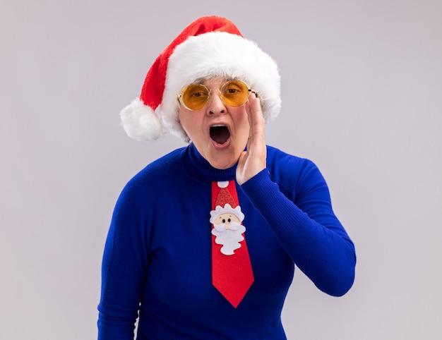 Geërgerd oudere vrouw in zonnebril met kerstmuts en kerststropdas houdt de hand dicht bij de mond om iemand te bellen Gratis Foto