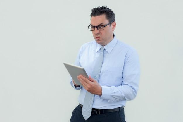 Geërgerde geschokte zakenman in oogglazen die tablet gebruiken Gratis Foto