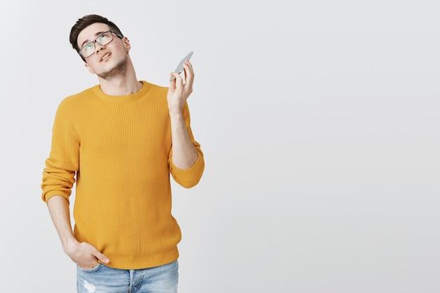 Geërgerde man die het gesprek wil beëindigen, zijn ogen wil rollen en zijn mobiele telefoon wil wegtrekken Gratis Foto