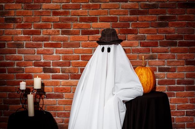 Geest in hoed poseren over bakstenen muur halloween party. Gratis Foto