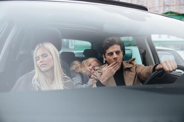 Geeuwende man zit in auto met slapende vrouw en dochter Gratis Foto