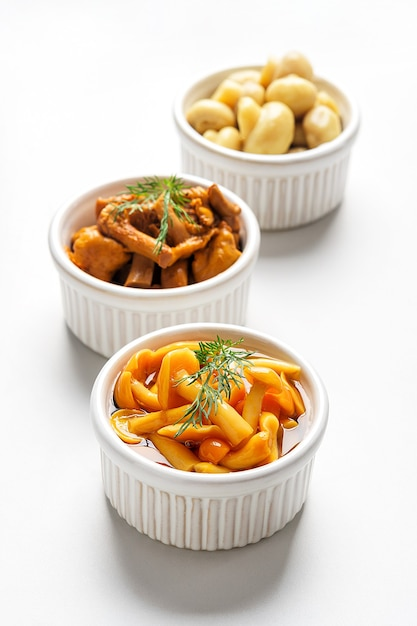 Gefermenteerd voedsel. ingeblikte champignons in kommen op een witte achtergrond. Premium Foto