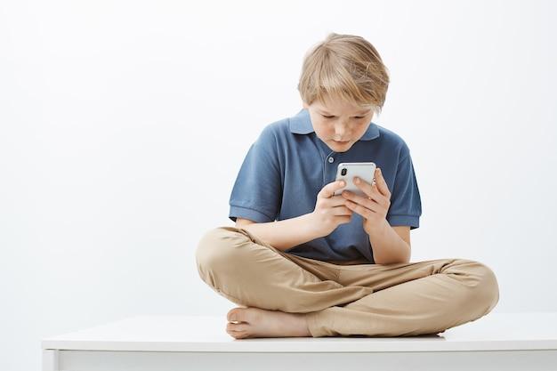 Gefrustreerd intense schattige jonge jongen met blond haar in casual outfit, zittend op gekruiste voeten Gratis Foto