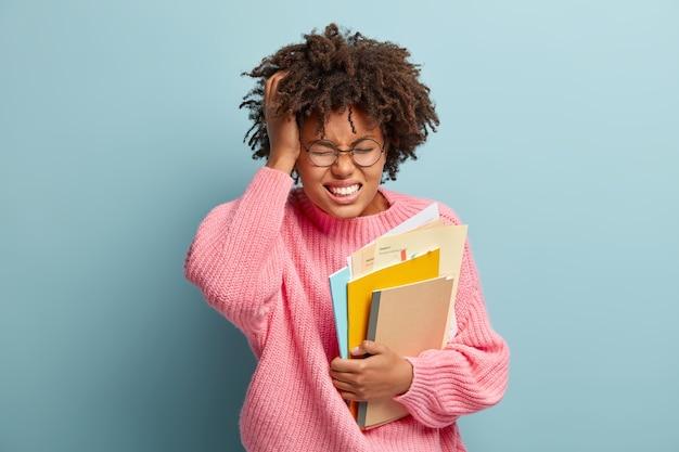 Gefrustreerd schoolmeisje heeft vreselijke hoofdpijn, fronst gezicht van pijn, studeert goed, houdt dagboek vast met papieren, draagt een ronde optische bril en roze trui, staat over blauwe muur, triest om de test te vergeten Gratis Foto