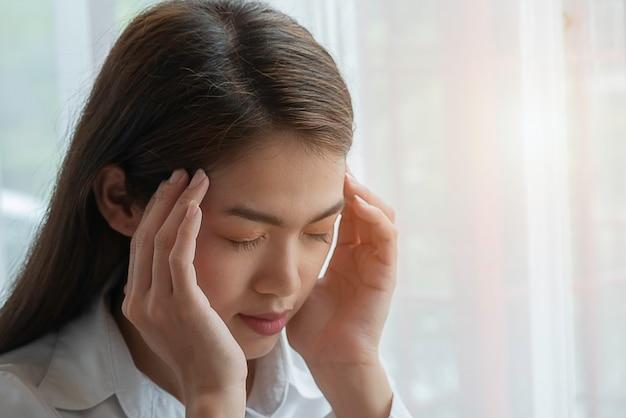 Gefrustreerde bedrijfsvrouw die aan hoofdpijn lijdt Premium Foto