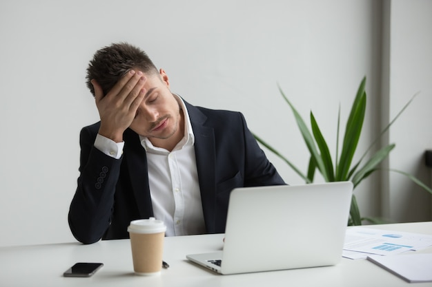 Gefrustreerde duizendjarige zakenman met sterke hoofdpijn moe van laptop werk Gratis Foto